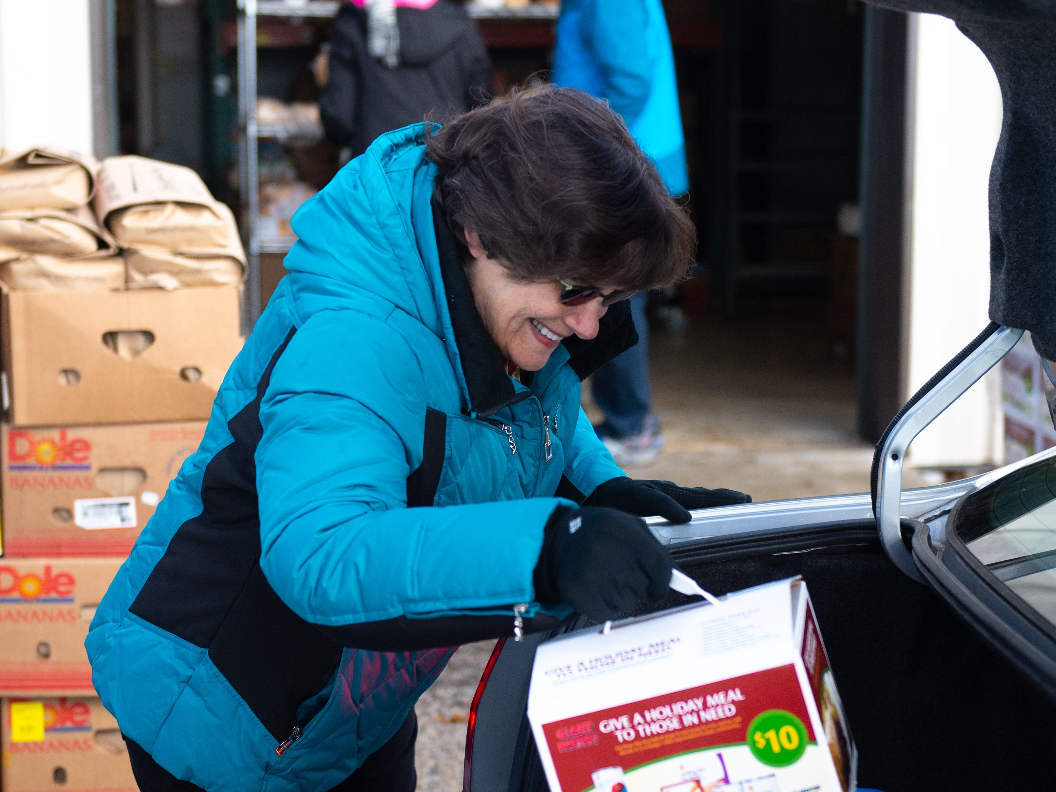 Berda McFadden places canned goods in the back of a very thankful visitor's car during the Thanksgiving food giveaway provided by New Hope Ministries. Donations came from businesses, schools, churches, civic groups and individuals.