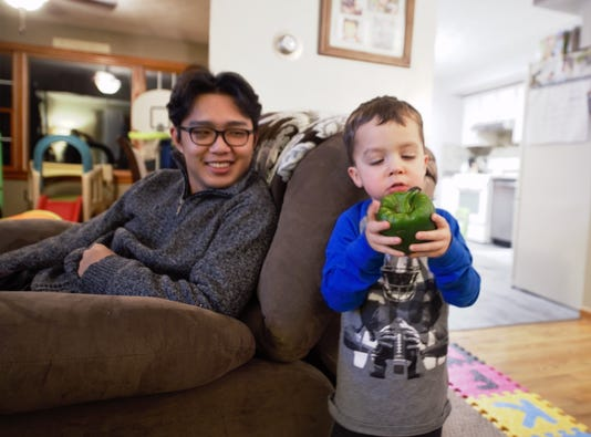 2- Johnny Zang, 17, (left) laughs as he watches Colton Harang, 3, inspect a green pepper he found in his family's refrigerator.
