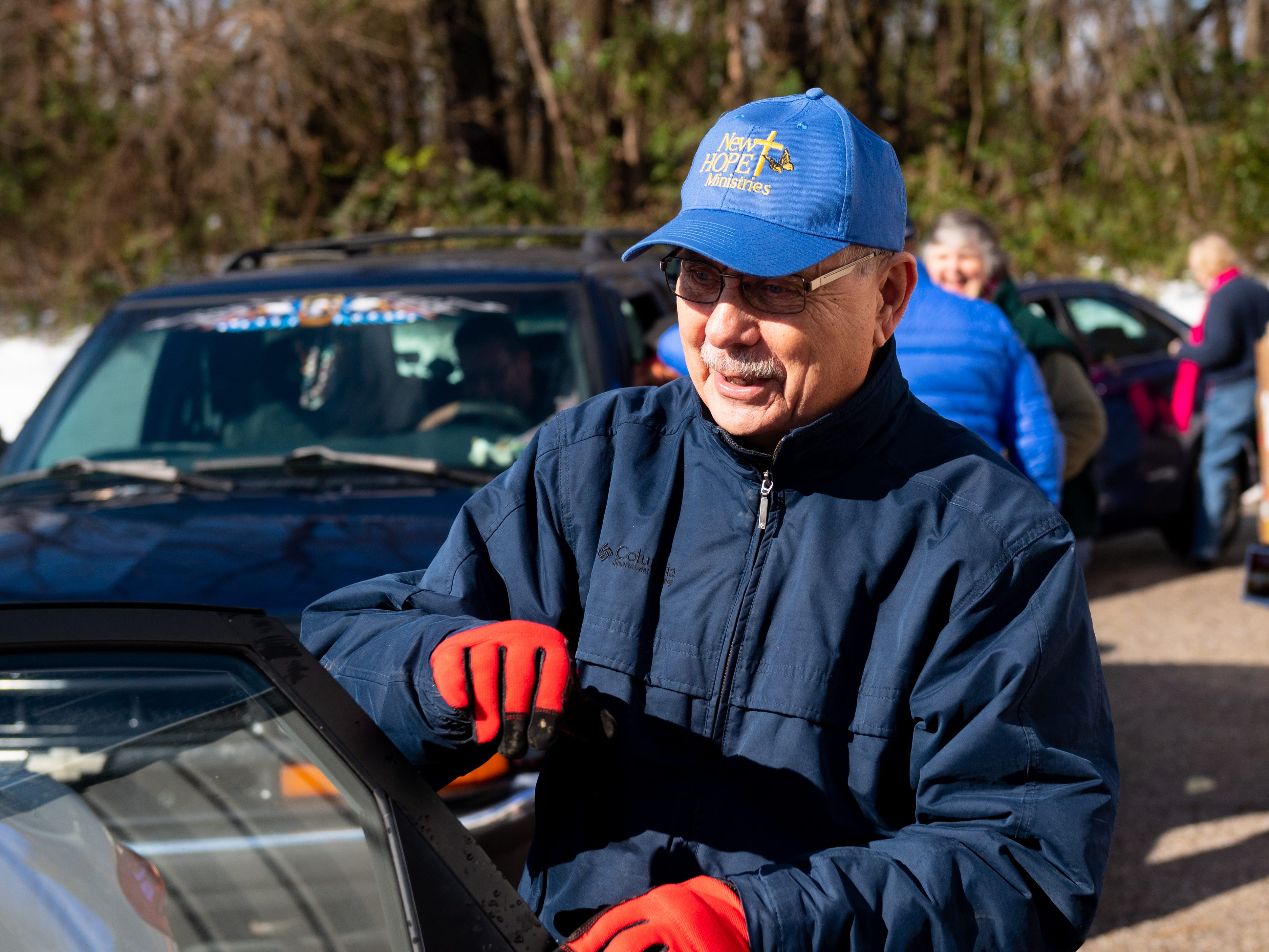 Charlie Wintermyer closes the door after all the food is packed inside of the vehicle during the Thanksgiving food giveaway provided by New Hope Ministries, November 16, 2018.