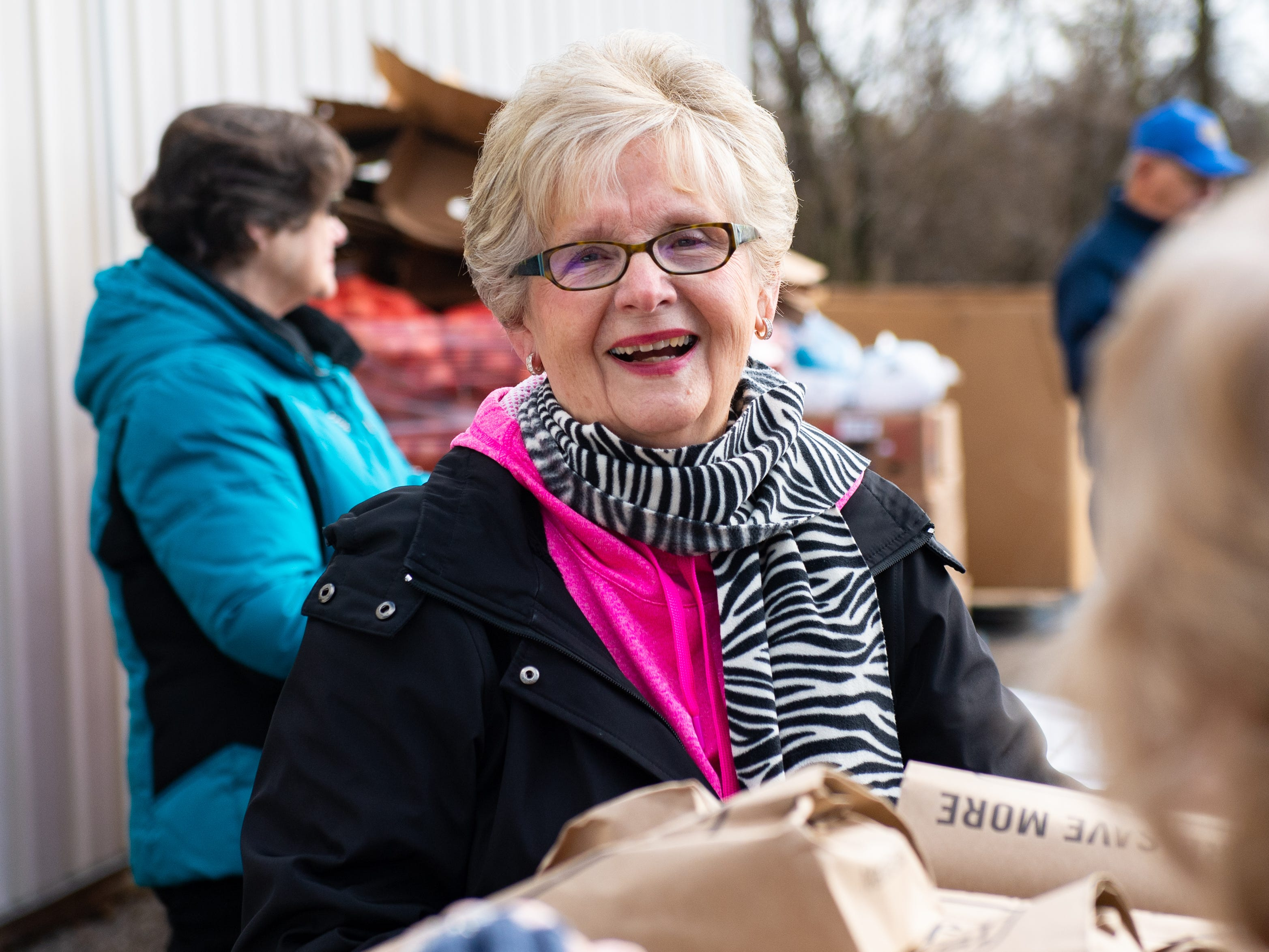 Bonnie Brodbeck is all smiles as she hands out food during the Thanksgiving food giveaway provided by New Hope Ministries, November 16, 2018.