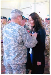 General Dan McNeill, a four-star general with the U.S. Army, pins a NATO medal for Annika Caldwell's service in the name of peace and freedom in Kabul in 2007.