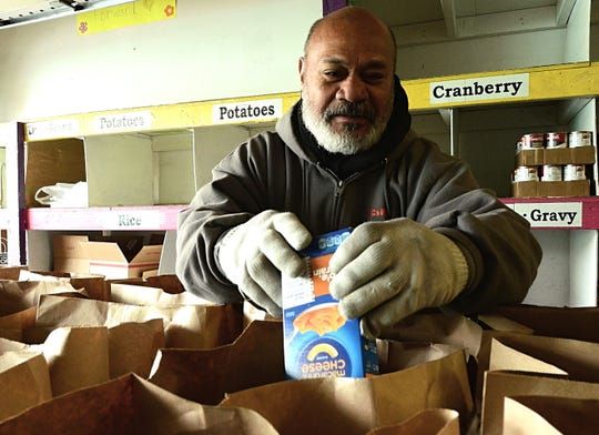 Isimeeli Malupo, 63, bags food for a holiday food drive on Nove. 16, 2018 at the Evelyn Mount Community Outreach.