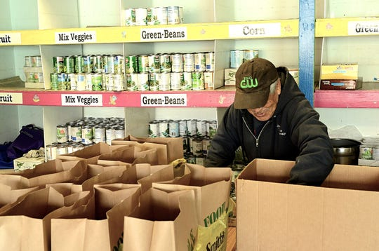 A volunteer bags cans of food on Nov. 16, 2018 at the Evelyn Mount Community Outreach center in Reno.