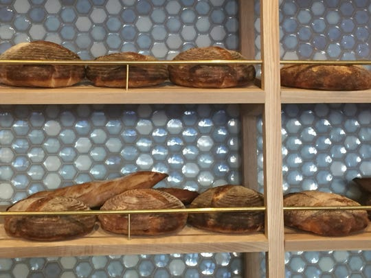 Baguettes and boules are displayed on shelves behind the front counter at Perenn Bakery.