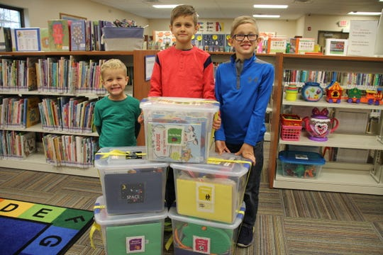 The brothers of the late Daniel Charland show off Daniel's Discovery Boxes – created in their brother's memory - at the Hamlin Library. They are, from left, Ezekiel, Samuel and Nathaniel Charland, of Kendall.