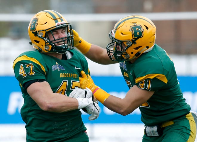 Brockport's Matt Szymanski is congratulated by Matt Arita after intercepting a pass and taking it to the end zone against Framingham in the second quarter at The College at Brockport.