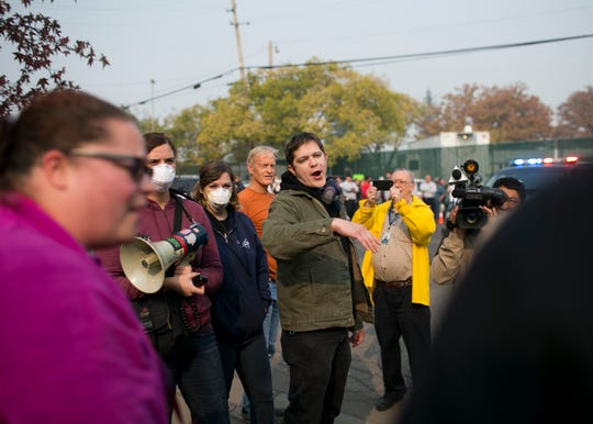Carlos Lopez, center, argues with President Trump supporters after the President arrives at the Camp Fire Incident Command Center at the Silver Dollar Fair Grounds in Chico, California on Nov. 17, 2018.