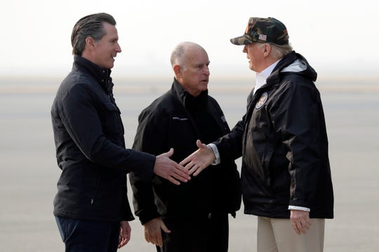 President Donald Trump greets California Gov.-elect Gavin Newsom as he arrives on Air Force One at Beale Air Force Base for a visit to areas impacted by the wildfires, Saturday, Nov. 17, 2018, at Beale Air Force Base, Calif., as Gov. Jerry Brown, stands at center. (AP Photo/Evan Vucci)