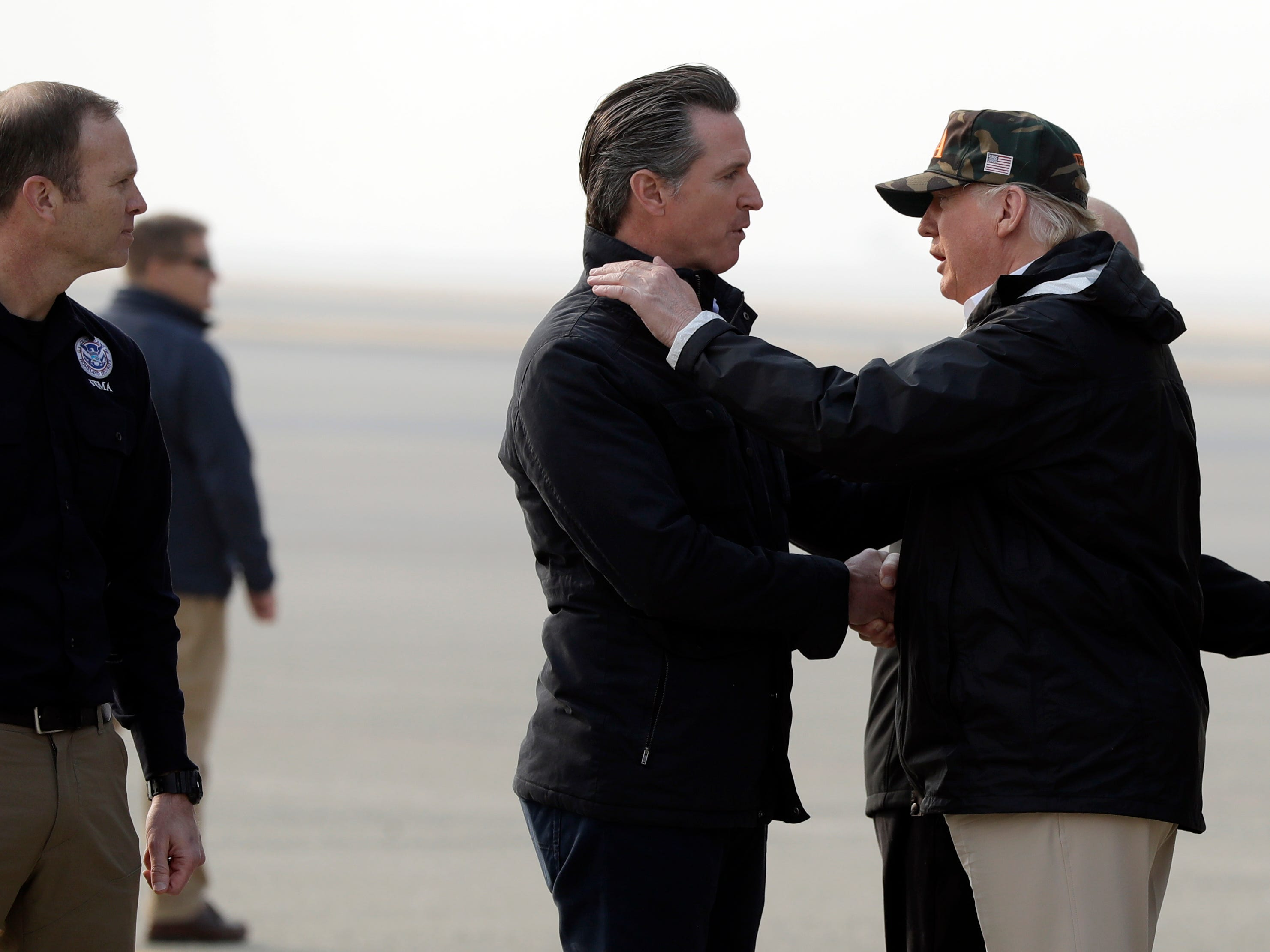 President Donald Trump greets California Gov.-elect Gavin Newsom as he arrives on Air Force One at Beale Air Force Base for a visit to areas impacted by the wildfires, Saturday, Nov. 17, 2018, at Beale Air Force Base, Calif. At left is Federal Emergency Management Agency administrator Brock Long (AP Photo/Evan Vucci) (AP Photo/Evan Vucci)