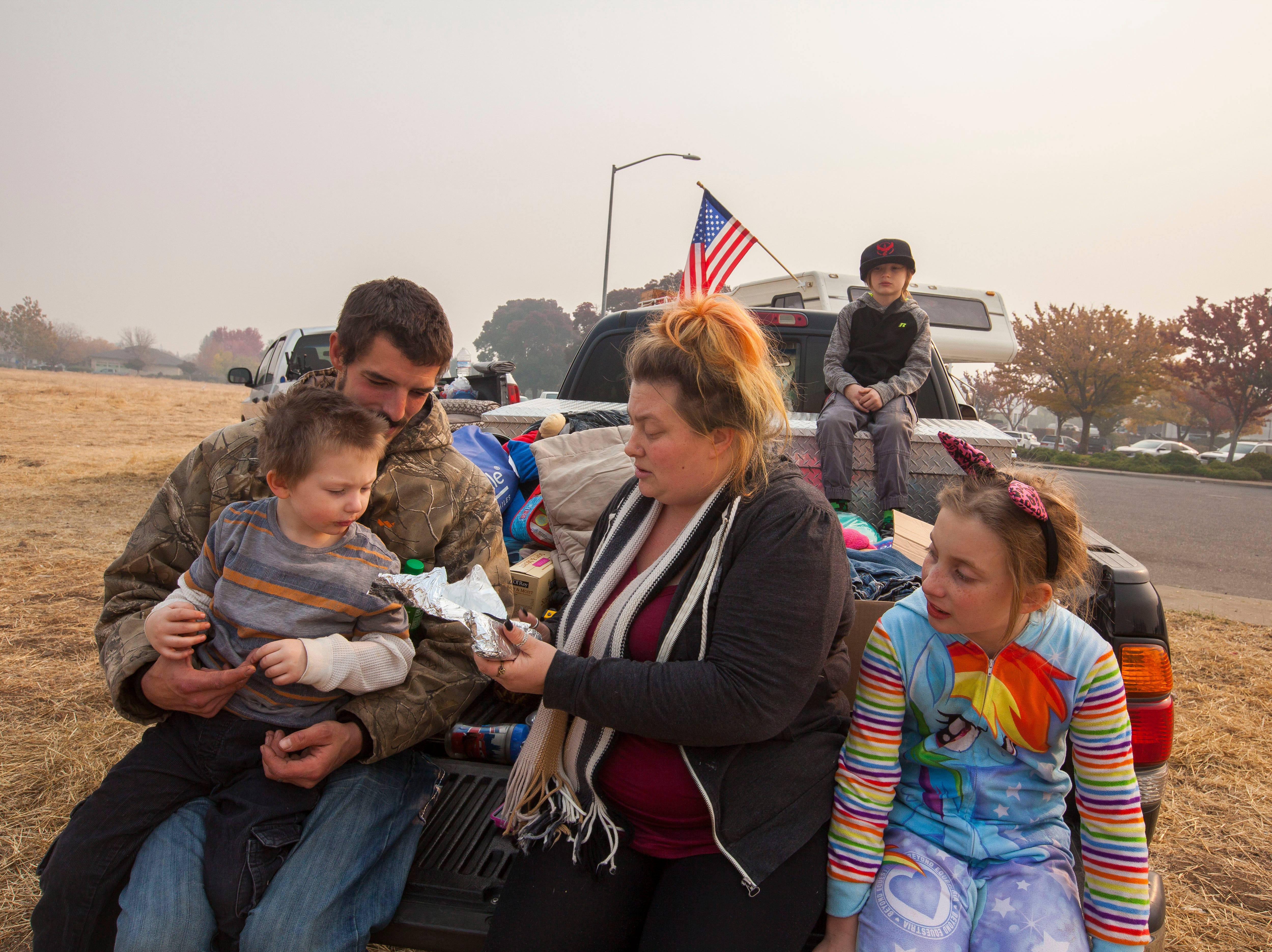 Ryan Belcher, left holds 4-year-old Bentley as Casey gives him some breakfast while their other children Zoeylee, 10 and Michael, 9, sit on the bed of a pick-up truck that Ryan's boss has loaned them. The Belcher family lost their home and vehicles in the Camp Fire. The children sleep in the truck at night and the parents share a small tent in a field next to the Walmart in Chico, CA.