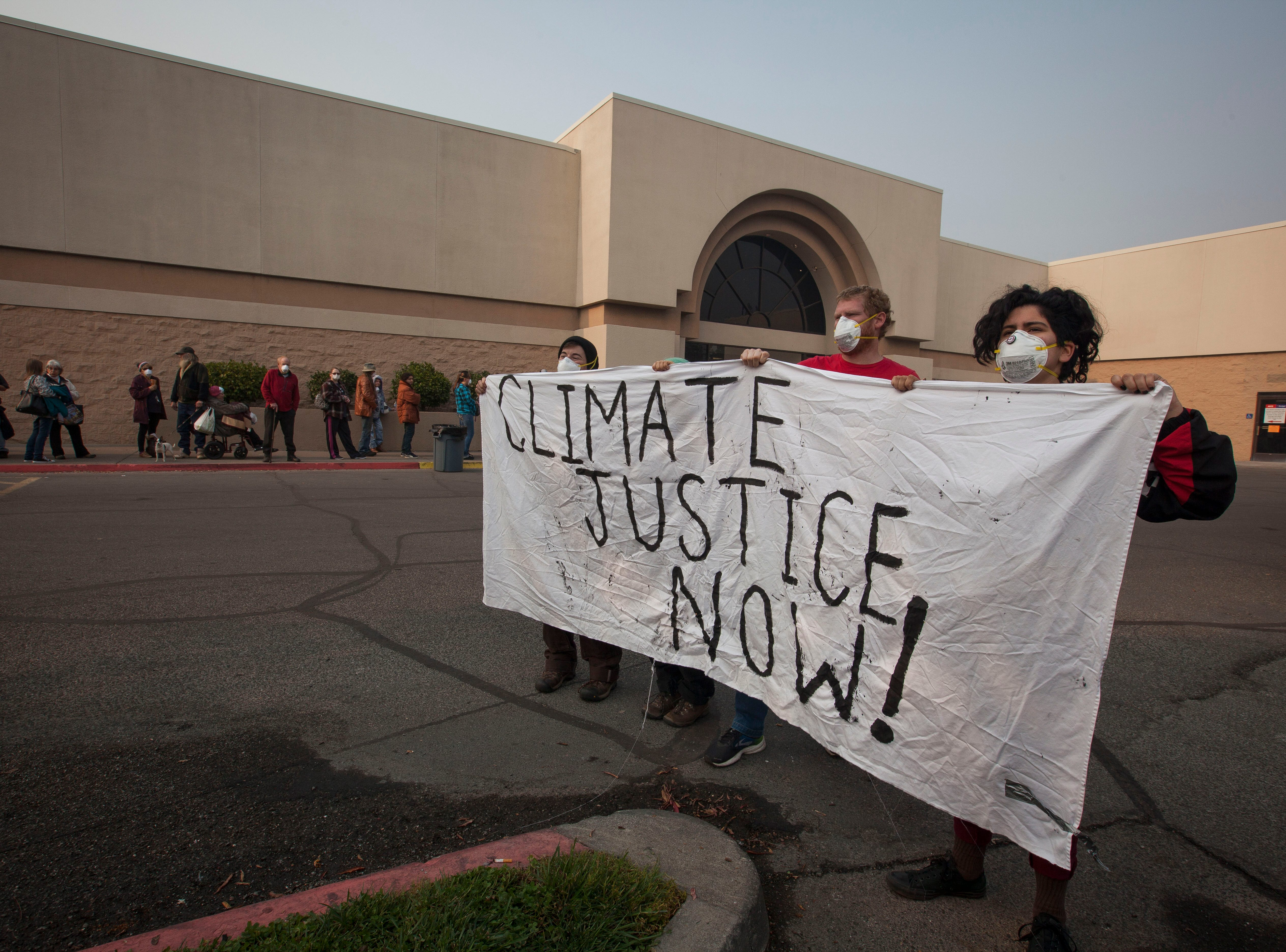 A group of activists hold a sign about climate change as people wait in a long line to get into the former Sears store in the Chico Mall, Saturday, Nov. 17, 2018. The empty store now houses FEMA and a host of other local, state and government agencies to help those affected by the Camp Fire.