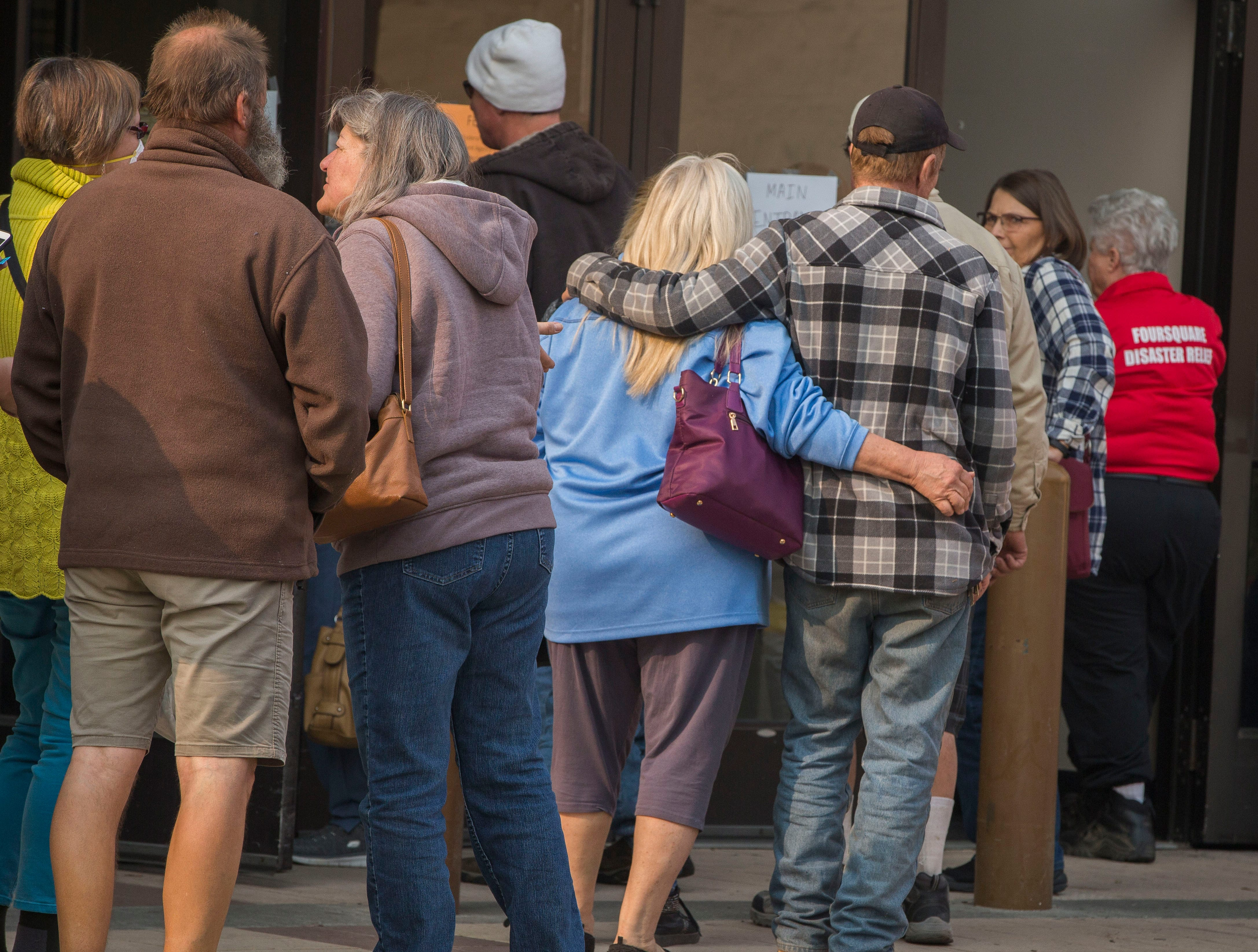 People wait in a long line to get into the former Sears store in the Chico Mall, Saturday, Nov. 17, 2018. The empty store now houses FEMA and a host of other local, state and government agencies to help those affected by the Camp Fire.