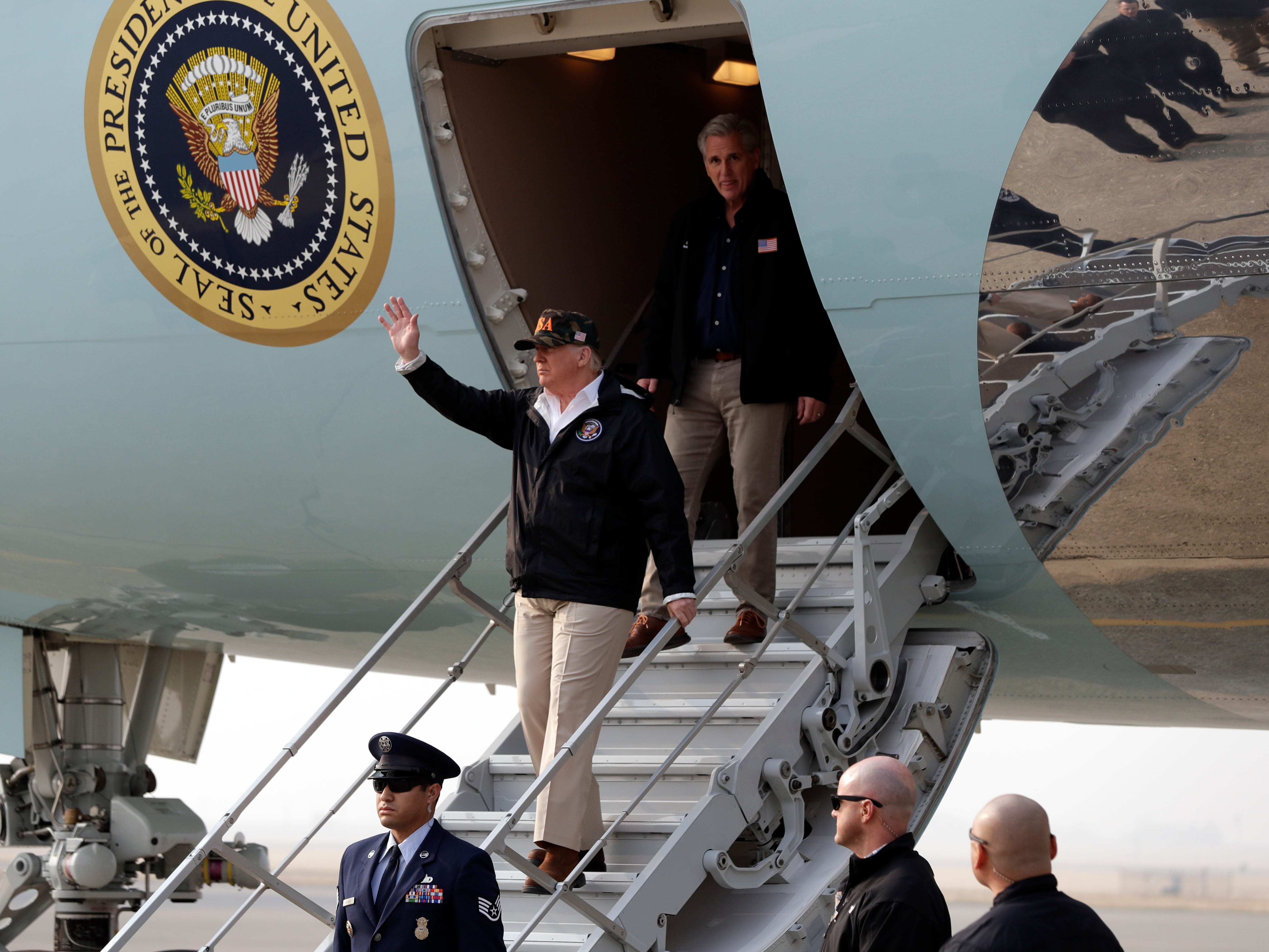 President Donald Trump waves as he arrives on Air Force One at Beale Air Force Base for a visit to areas impacted by the wildfires, Saturday, Nov. 17, 2018, at Beale Air Force Base, Calif.  He is followed by House Majority Leader Kevin McCarthy of Calif. (AP Photo/Evan Vucci)