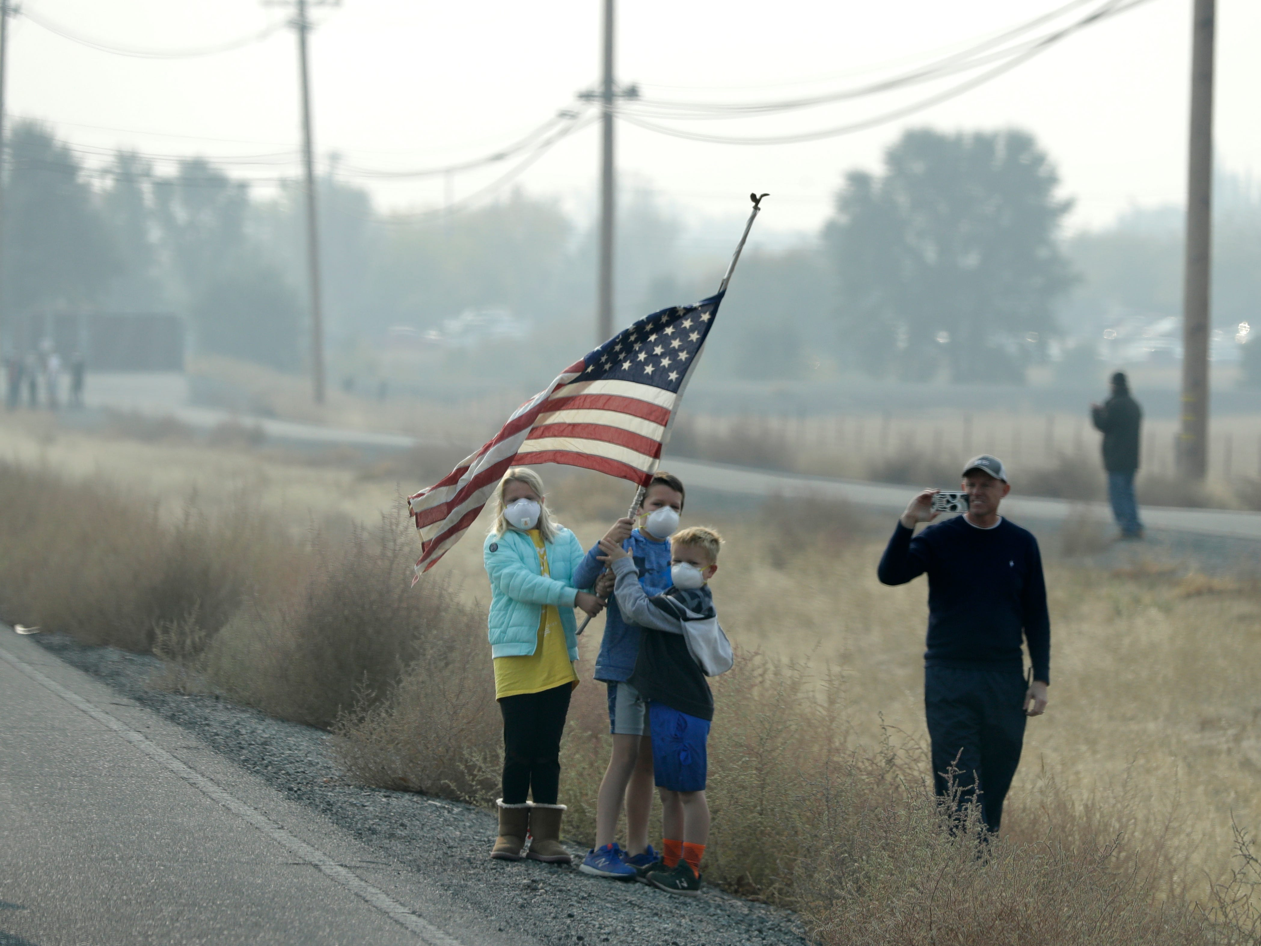People stand on the side of the road holding an American flag as the motorcade of President Donald Trump drives through Chico, Calif., on a visit to areas affected by the wildfires, Saturday, Nov. 17, 2018. (AP Photo/Evan Vucci)