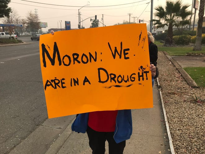 A protester in Chico holds up a signs she made for President Donald Trump, who landed in California Saturday to tour damage from the Camp Fire.