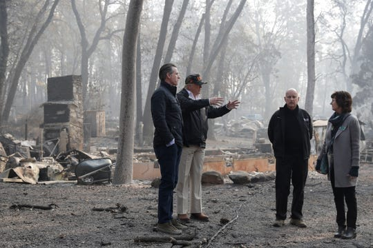 President Donald Trump talks with Jody Jones, Mayor of Paradise, as California Gov. Jerry Brown, second from right and Gov.-elect Gavin Newsom, left, during a visit to a neighborhood impacted by the wildfires, Saturday, Nov. 17, 2018, in Chico, Calif.