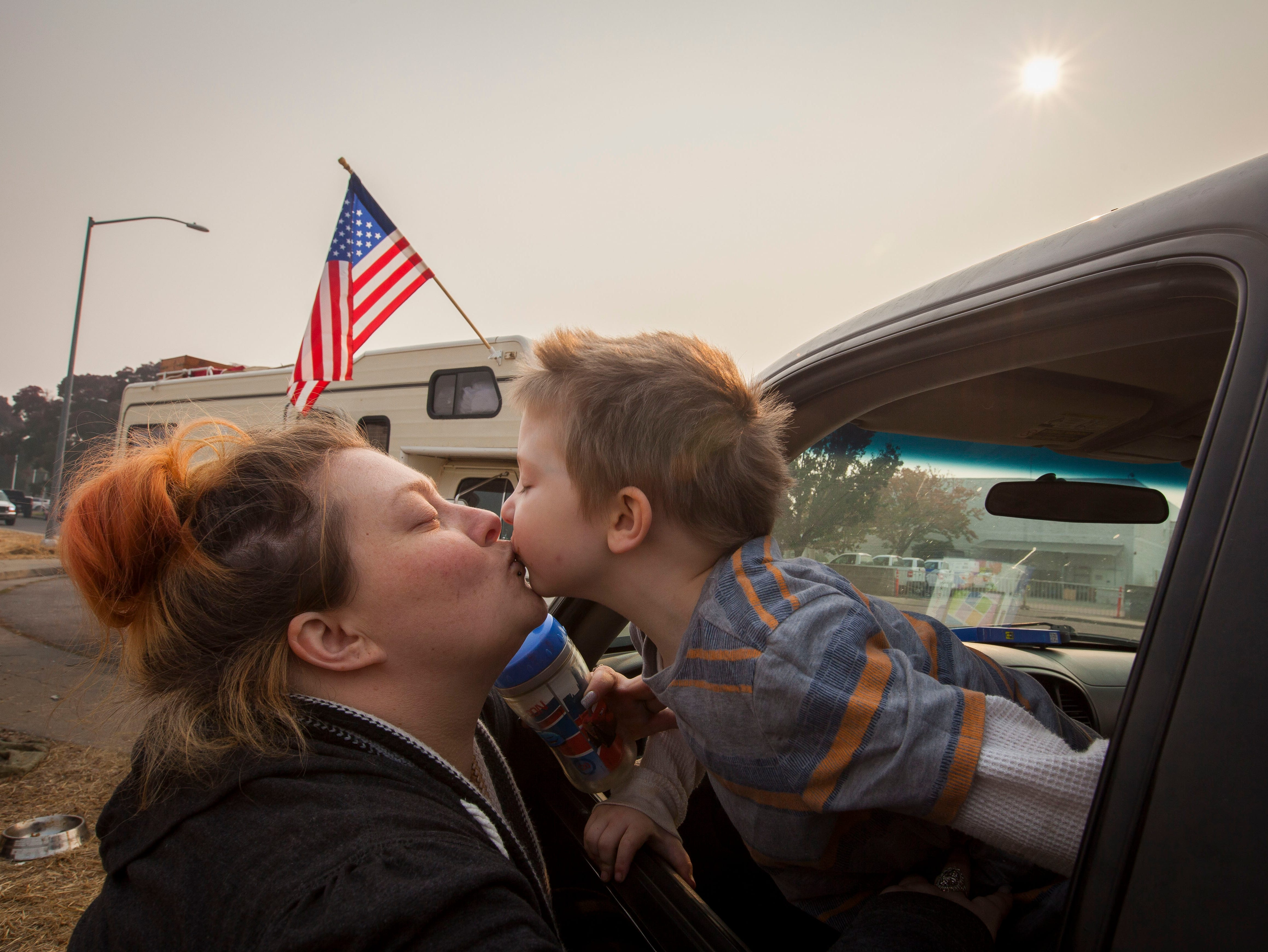 Casey Belcher gets a kiss from her 4-year-old son Bentley who was sitting in the cab of a pick-up truck. Casey, her husband and their three children lost their house and vehicles in the Camp Fire. Her husband's boss has given them a work truck to drive until the family can get situated. The children sleep in the truck at night and the parents share a small tent in a field next to the Walmart in Chico, CA.
