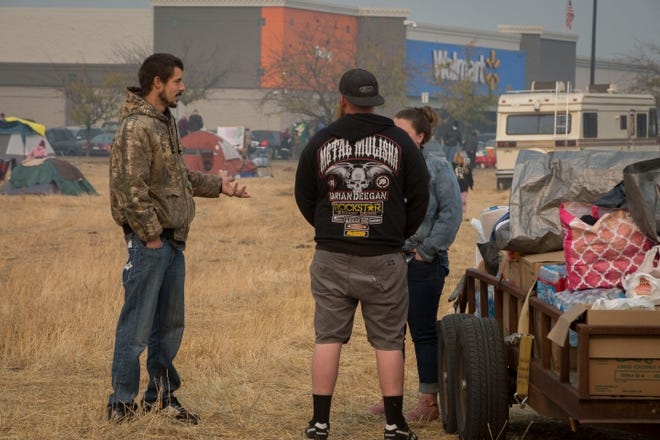 Ryan Belcher, left, thanks a couple of volunteers who collected items to bring and donate to those who are camping at the tent city that has formed at the Walmart in Chico, CA, Saturday Nov. 17, 2018. Ryan, his wife Casey and their three children lost their home and vehicles to the Camp Fire.