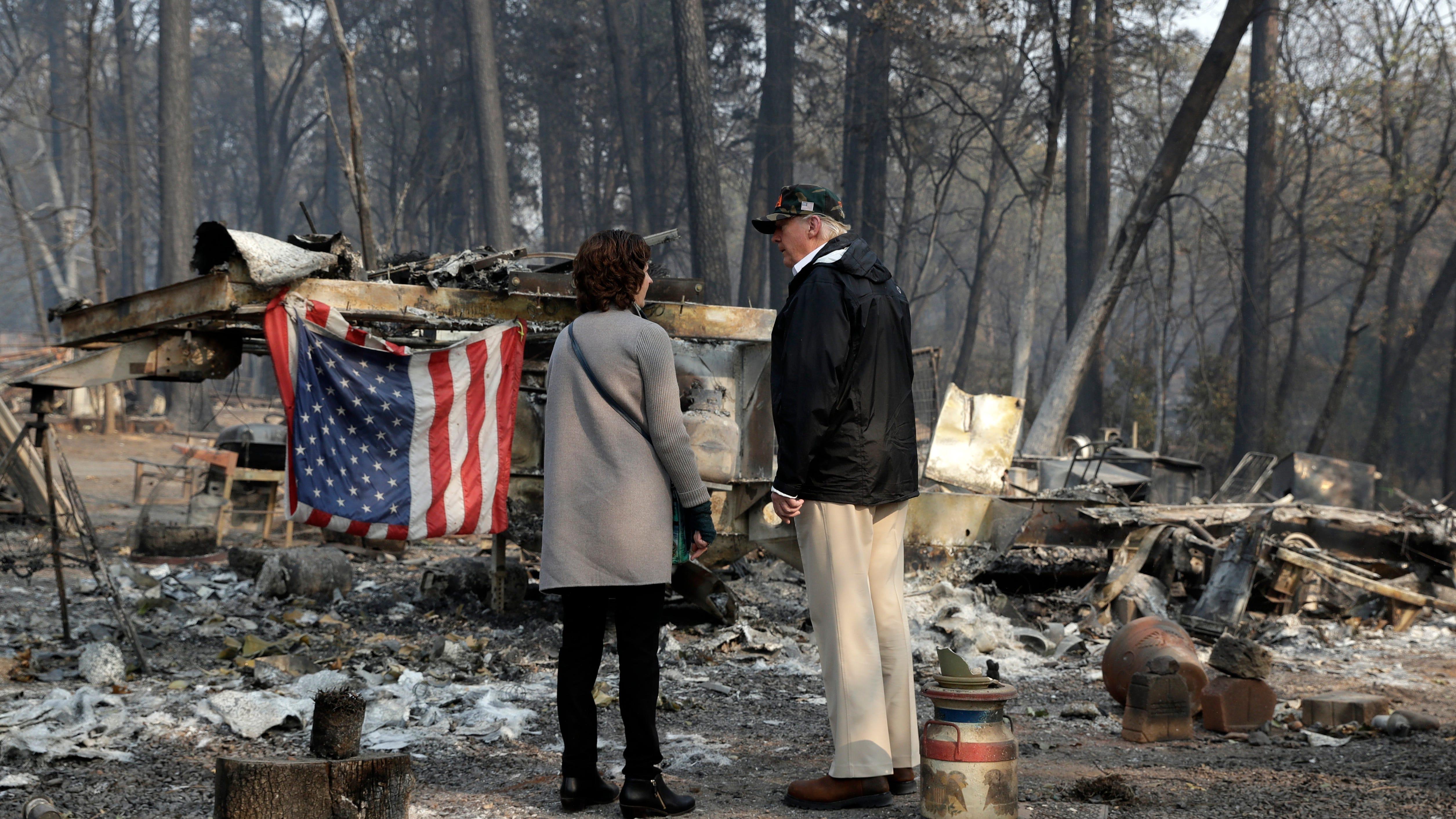 President Donald Trump talks to Mayor Jody Jones as he visits a neighborhood impacted by the wildfires, Saturday, Nov. 17, 2018, in Paradise, Calif. (AP Photo/Evan Vucci)