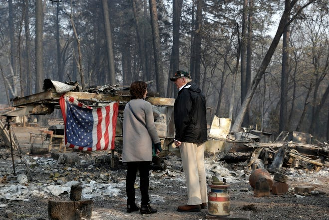 President Donald Trump talks to Mayor Jody Jones as he visits a neighborhood impacted by the wildfires, Saturday, Nov. 17, 2018, in Paradise, Calif. (AP Photo/Evan Vucci)