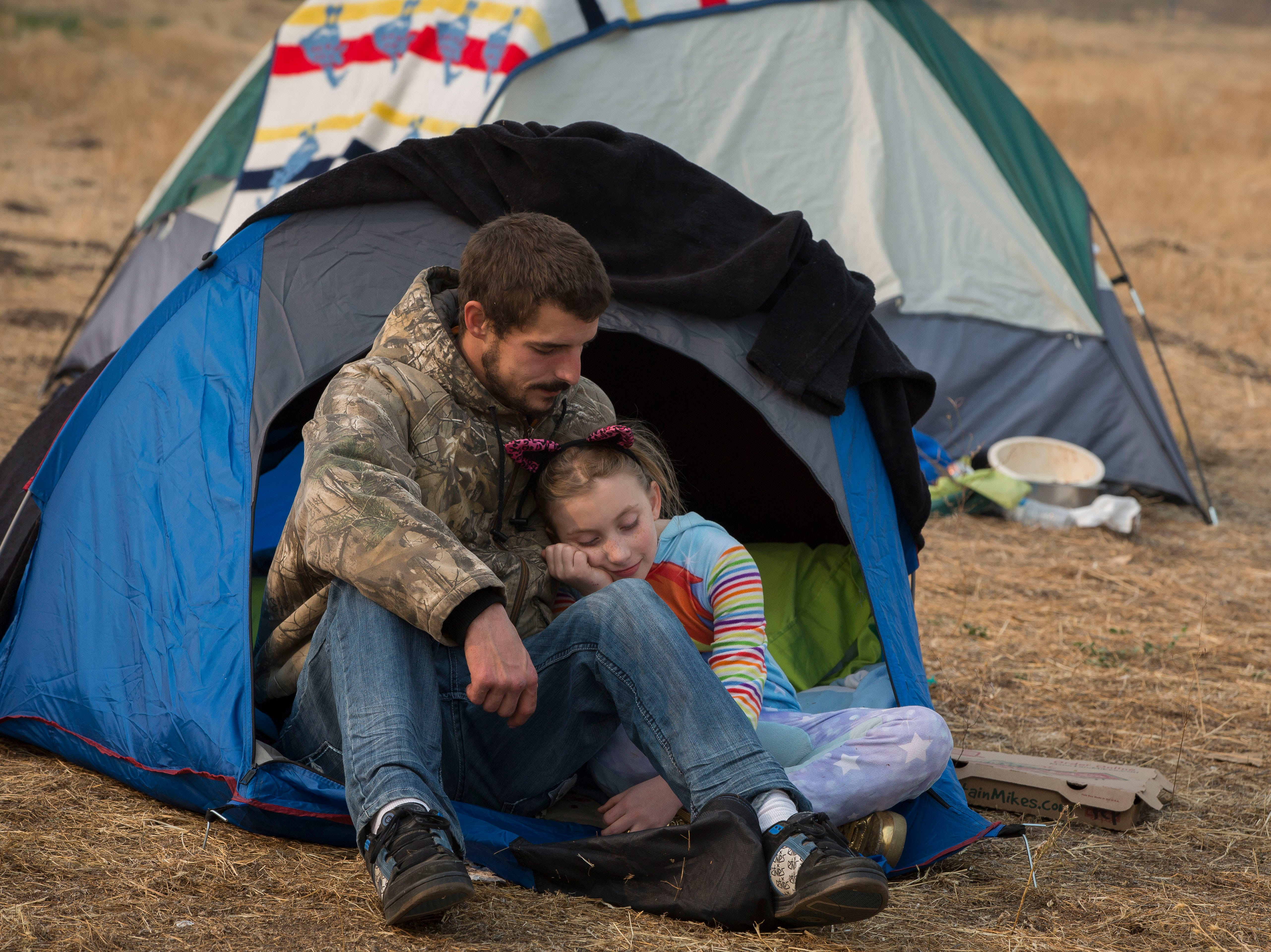 Ryan Belcher, 9, left comforts his daughter Zoeylee, 10, where they are camping with their family at the Walmart in Chico, CA, Saturday Nov. 17, 2018. The Belcher family lost their home and vehicles to the Camp Fire.