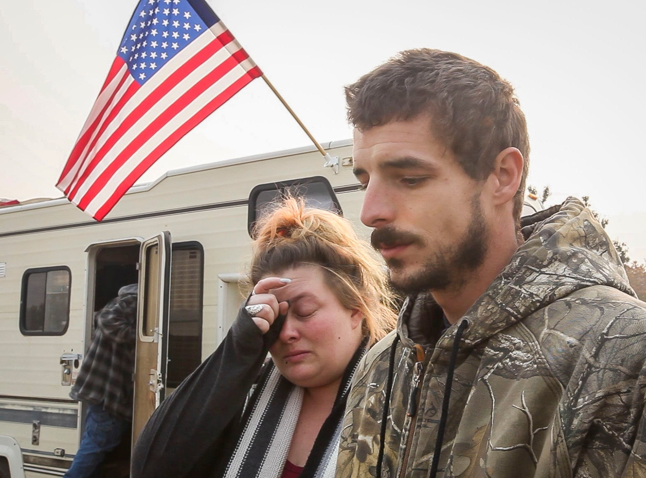 Ryan Belcher, left and his wife Casey sit next to a pick-up truck that Ryan's boss has loaned them. The Belcher family lost their home and vehicles in the Camp Fire. The children sleep in the truck at night and the parents share a small tent in a field next to the Walmart in Chico, CA.