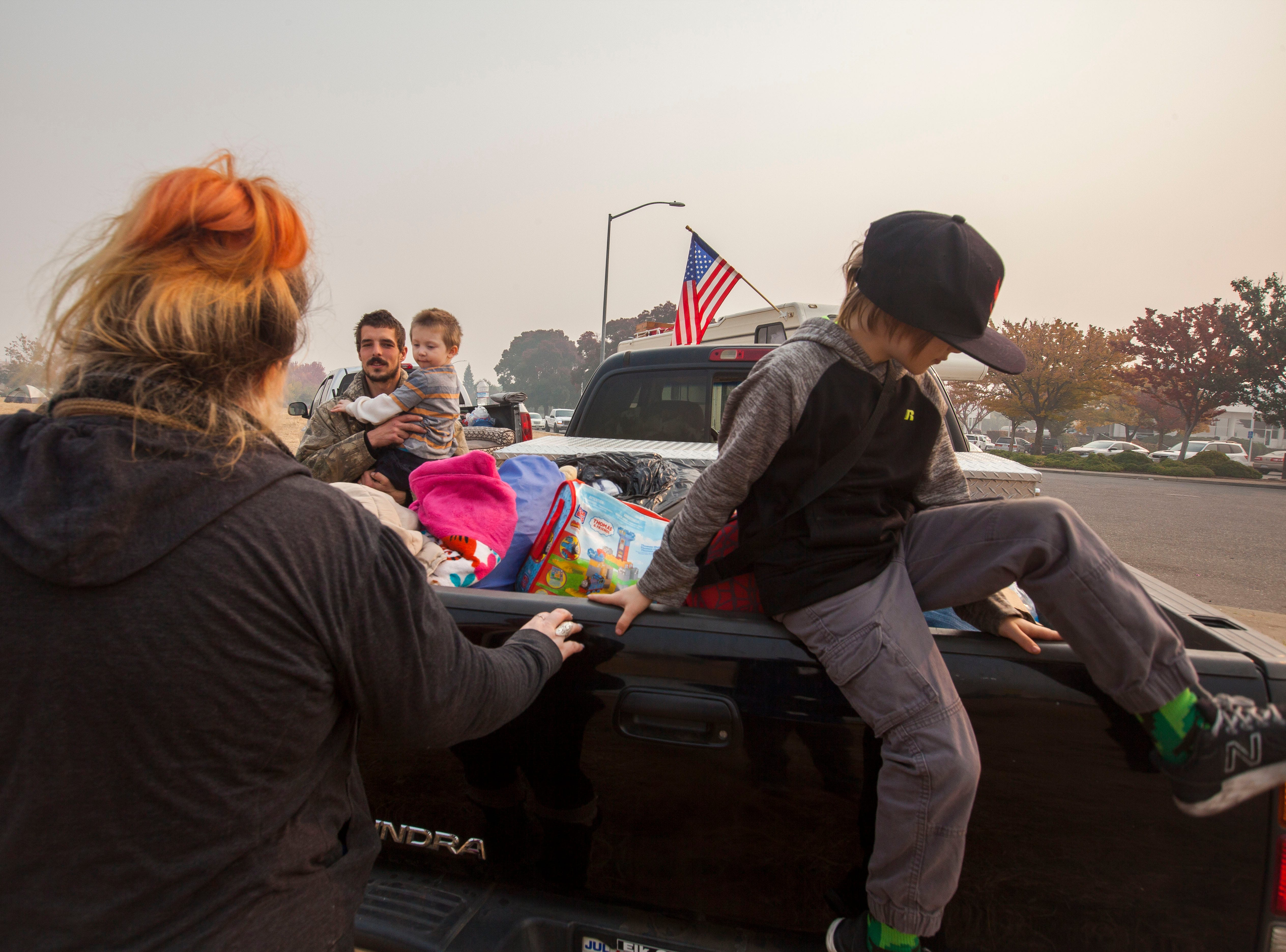 Ryan Belcher carries his 4-year-old son Bentley while talking to his wife Casey and their 9-year-old son Michael. Casey, Ryan and their three children lost their home and vehicles in the Camp Fire. Her husband's boss has given them a work truck to drive until the family can get situated. The children sleep in the truck at night and the parents share a small tent in a field next to the Walmart in Chico, CA.