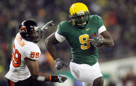 Dec 3, 2009; Eugene, OR, USA;  Oregon Ducks running back LeGarrette Blount (9) runs past Oregon State Beavers linebacker Dwight Roberson (59) for a touchdown in the third quarter at Autzen Stadium. Mandatory Credit: Craig Mitchelldyer-USA TODAY Sports