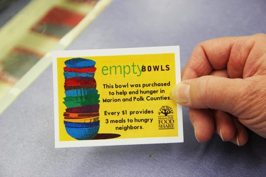 Pam Prosise, outreach coordinator for the Willamette Art Center, holds a card people can include when giving a bowl as a gift so the recipient is aware of the impact it made on the community. Photographed on Saturday, Nov. 17.