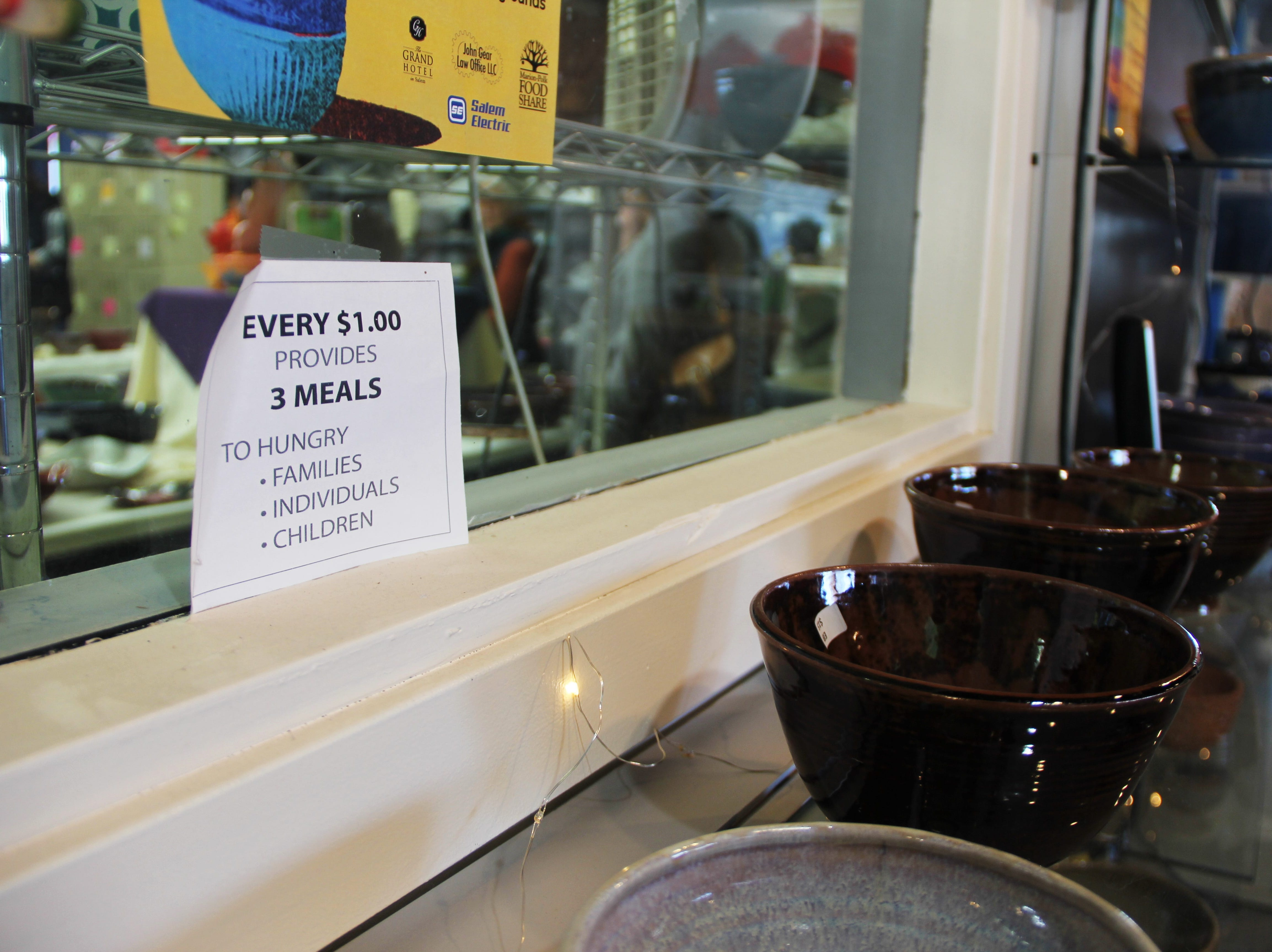 A sign photographed on Saturday, Nov. 17, explains how every dollar spent at the Willamette Art Center's Empty Bowls fundraiser provides three meals for members of the community.