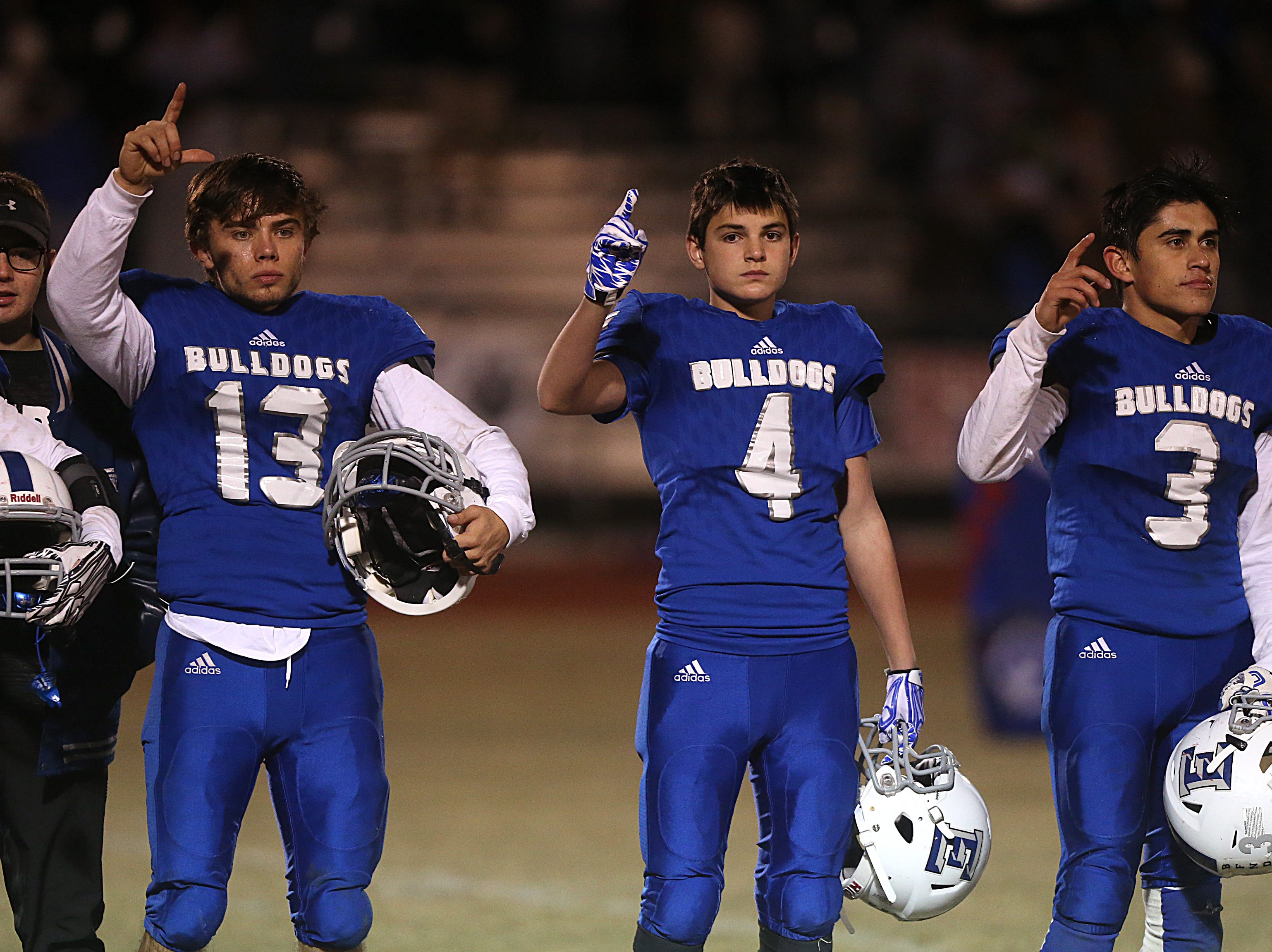 Eden Bulldogs hold their hands up during their school song Friday, Nov. 16, 2018 in Santa Anna. Eden lost to Gorman 20 to 68.