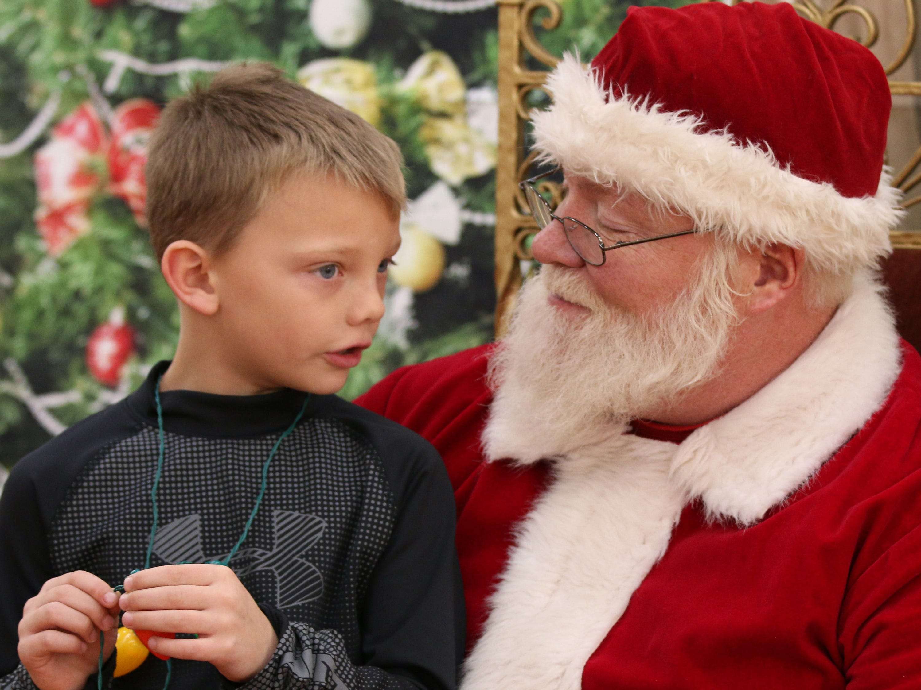 Carter Rekowski, 6, of Hingham, Wis., tells Santa Claus about his Christmas wishes at Festival Foods, Saturday November 17, 2018, in Sheboygan, Wis. Santa was part of the Salvation Army's Red Kettle Campaign kickoff.