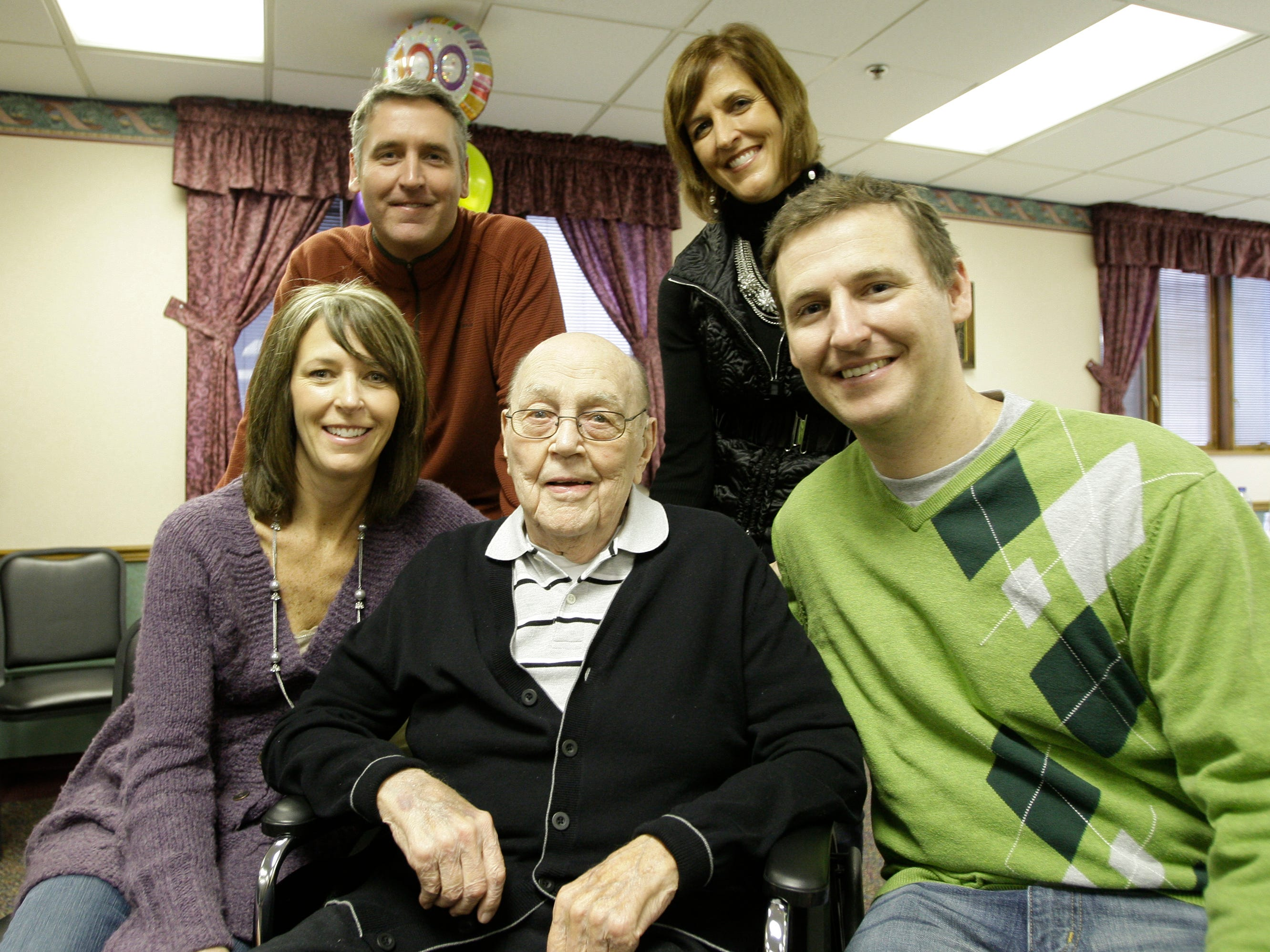 Sheboygan Redskins coach Frank Zummach sits in a wheelchair  while posing with his family Saturday January 28, 2011 during his 100th birthday party at the Sheboygan Senior Community, in Sheboygan, Wis. About 35 family members came to the event.