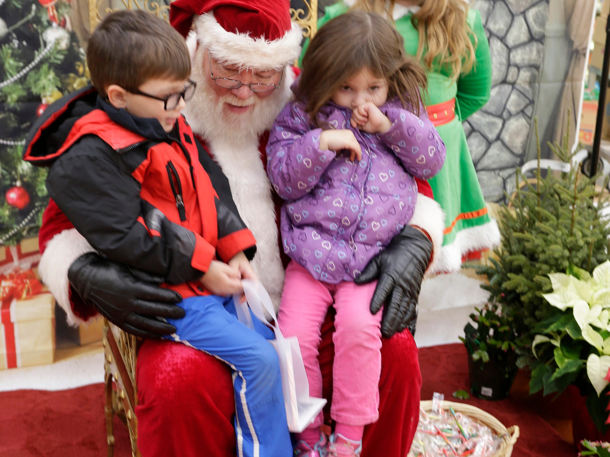 Nolan Zorn, 4, left, and his sister Everly, 3, take turns telling Santa Claus, center, what they want for Christmas during the Salvation Army Kettle Campaign kickoff at Festival Foods, Saturday November 17, 2018, in Sheboygan, Wis.