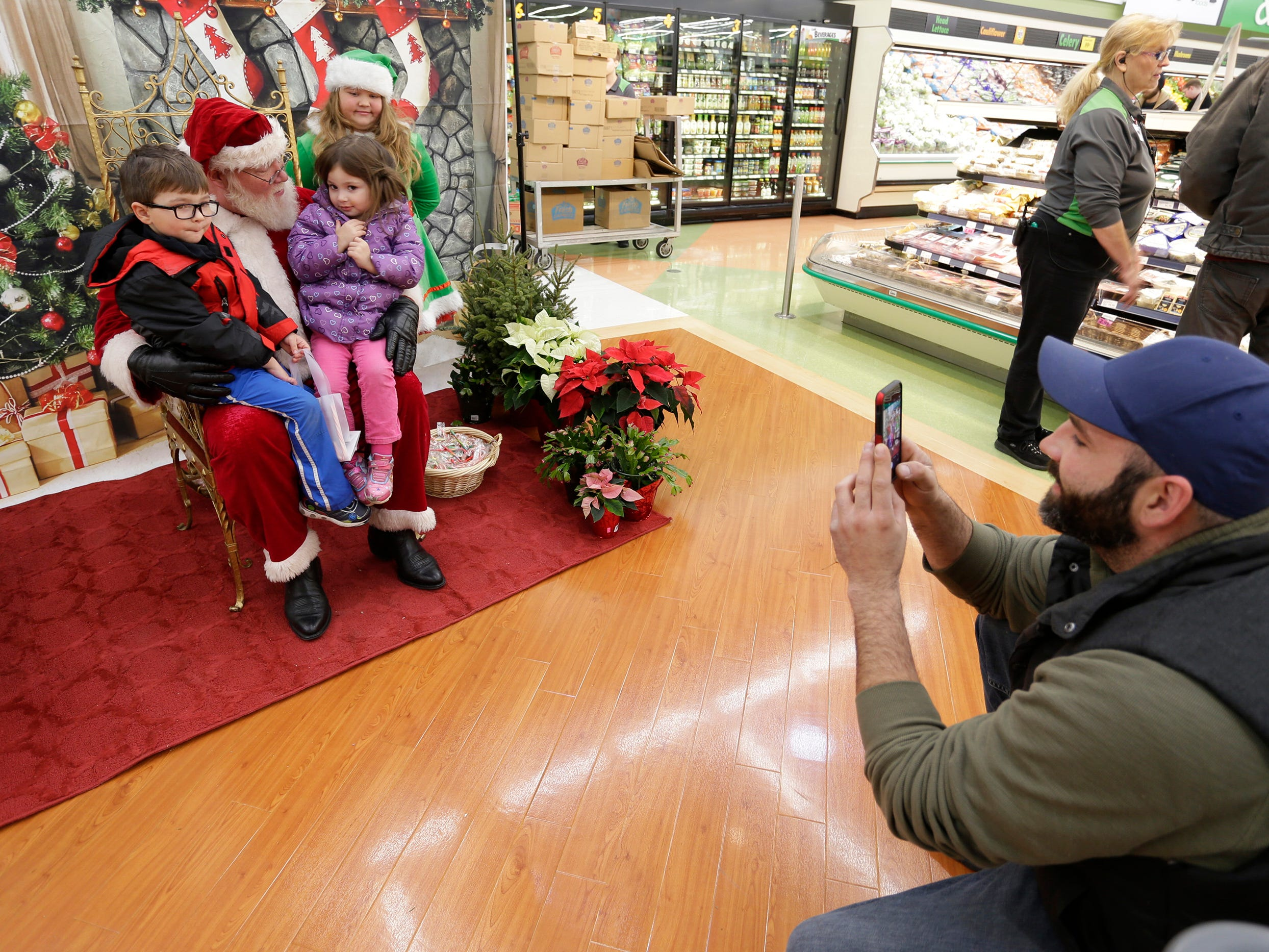Brandon Zorn of Sheboygan, right, snaps a photo of his children Nolan, 4, and Everly 3, while taking in some shopping at Festival Foods, Saturday November 17, 2018, in Sheboygan, Wis. Santa Claus was at the event which was part of the Salvation Army's annual Kettle Campaign kickoff.