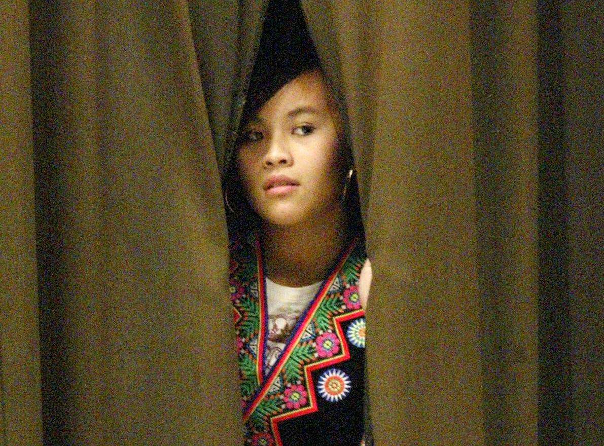 A Hmong girl peers from the curtains at the Sheboygan Armory during the Hmong New Year, Saturday November 22, 2006, in Sheboygan, Wis.