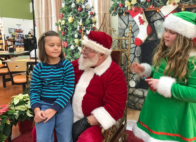 Emily Shelton, 8, of Plymouth, Wis., ponders her Christmas wish with Santa Claus and his elf at Festival Foods, Saturday November 17, 2018, in Sheboygan, Wis.  Santa was part of the Salvation Army's Red Kettle Campaign kickoff.