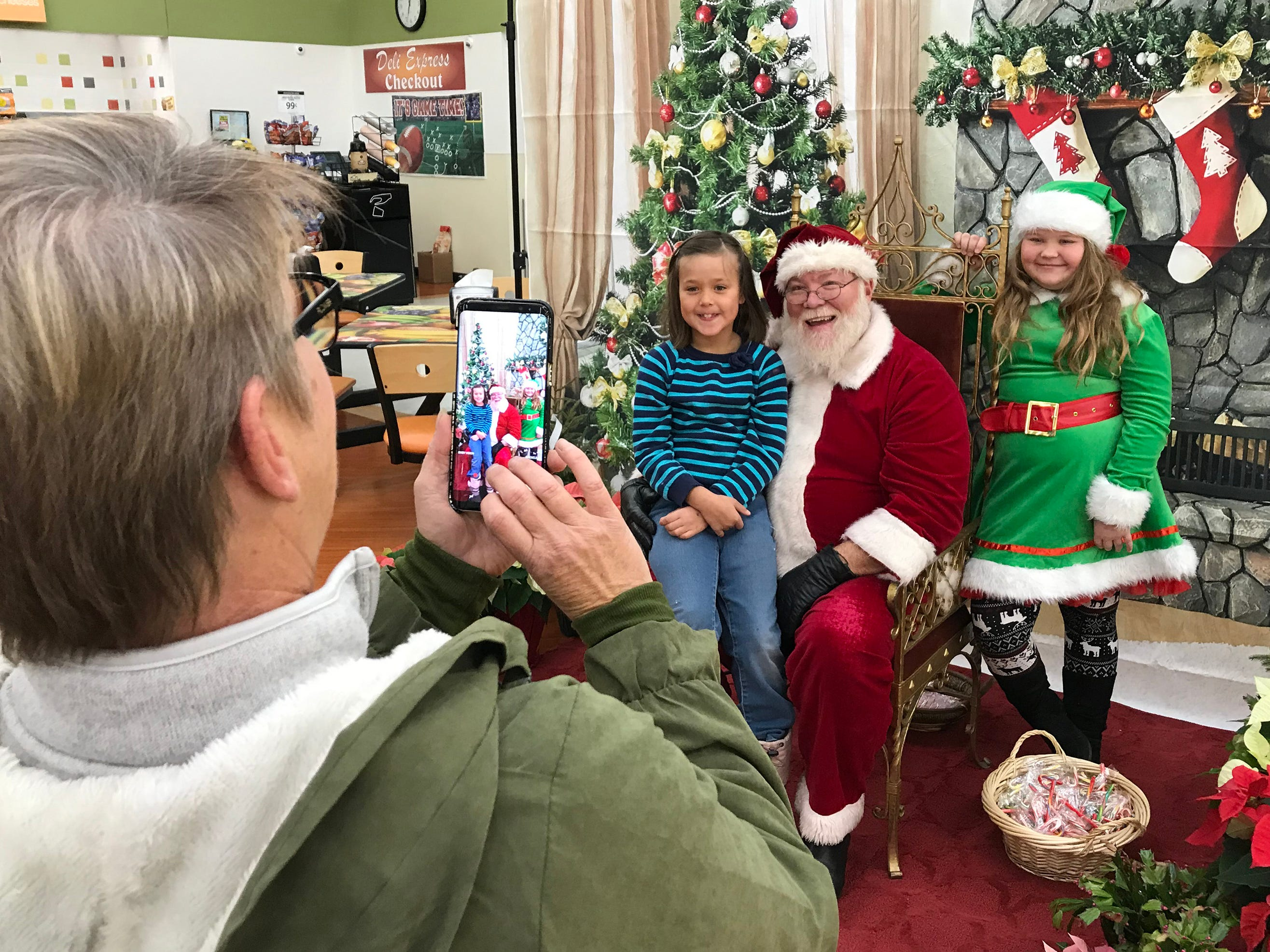 Laura Cortinaz of Plymouth, Wis, left, snaps a photo of granddaughter Emily Shelton, 8, of Plymouth with Santa Claus and his elf at Festival Foods, Saturday November 17, 2018, in Sheboygan, Wis. Santa was part of the Salvation Army's Red Kettle Campaign kickoff.