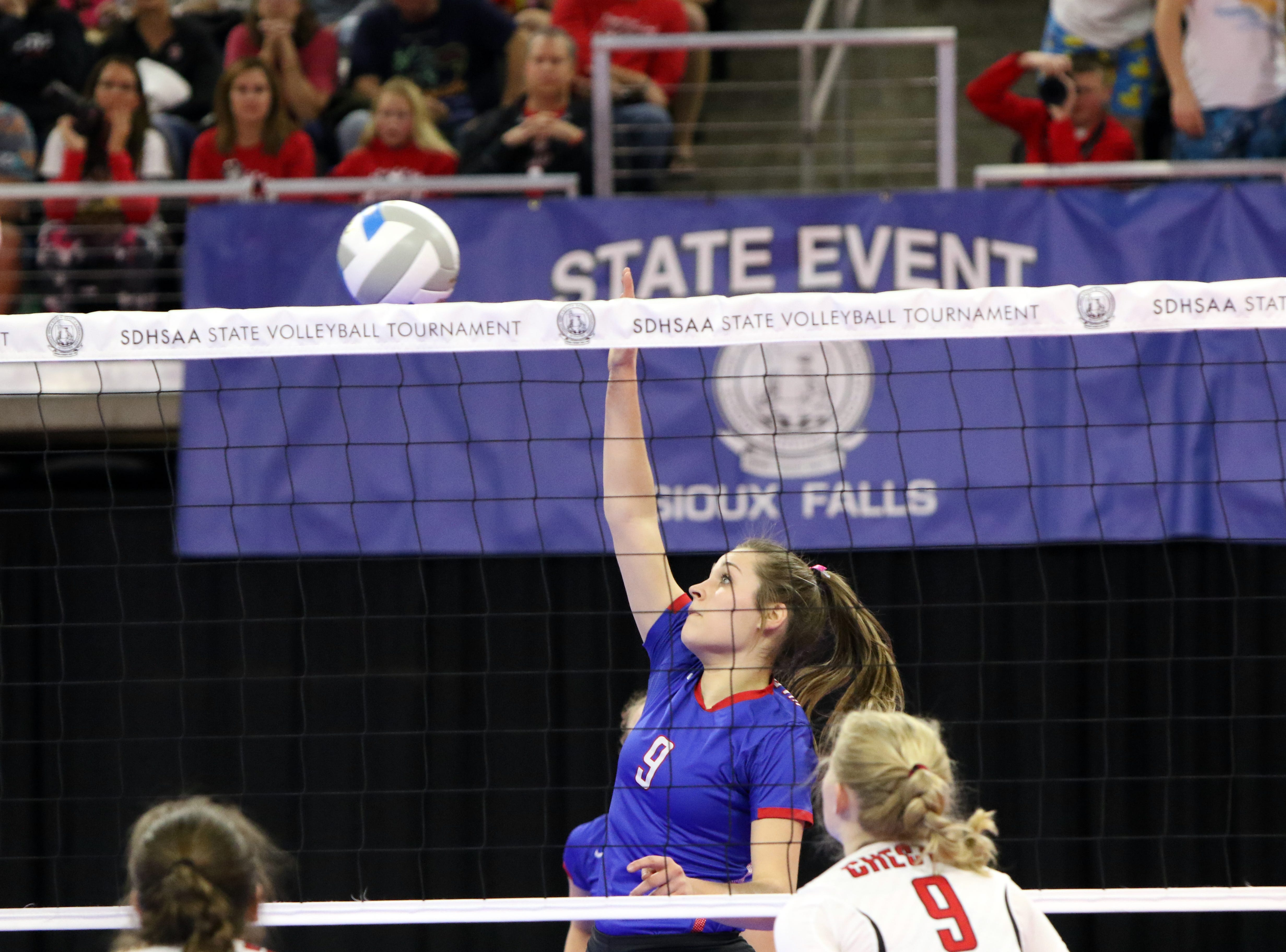 Ashley Fischbach of Warner taps the ball over the net between Ella Pry (9) and Jennilee Hoyer of Chester Area during the Class B semifinals on Friday in Sioux Falls.