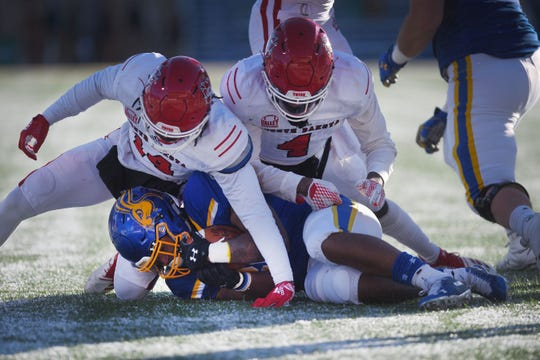 SDSU's Mikey Danielis is taken down by USD's Michael Fredrick (14) and Elijah Reed (4) during the game Saturday, Nov. 17, at Dana Dykhouse Stadium stadium in Brookings.