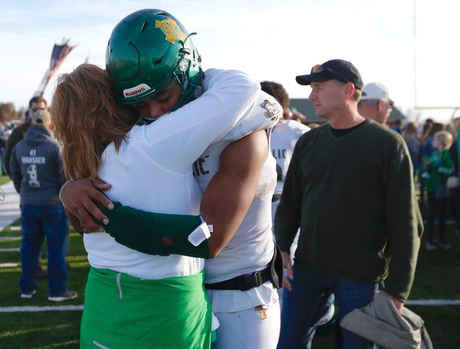 Springfield Catholic quarterback Tyson Riley hugs his mom Nikki Riley after their Irish's loss to Mount Vernon on Saturday.