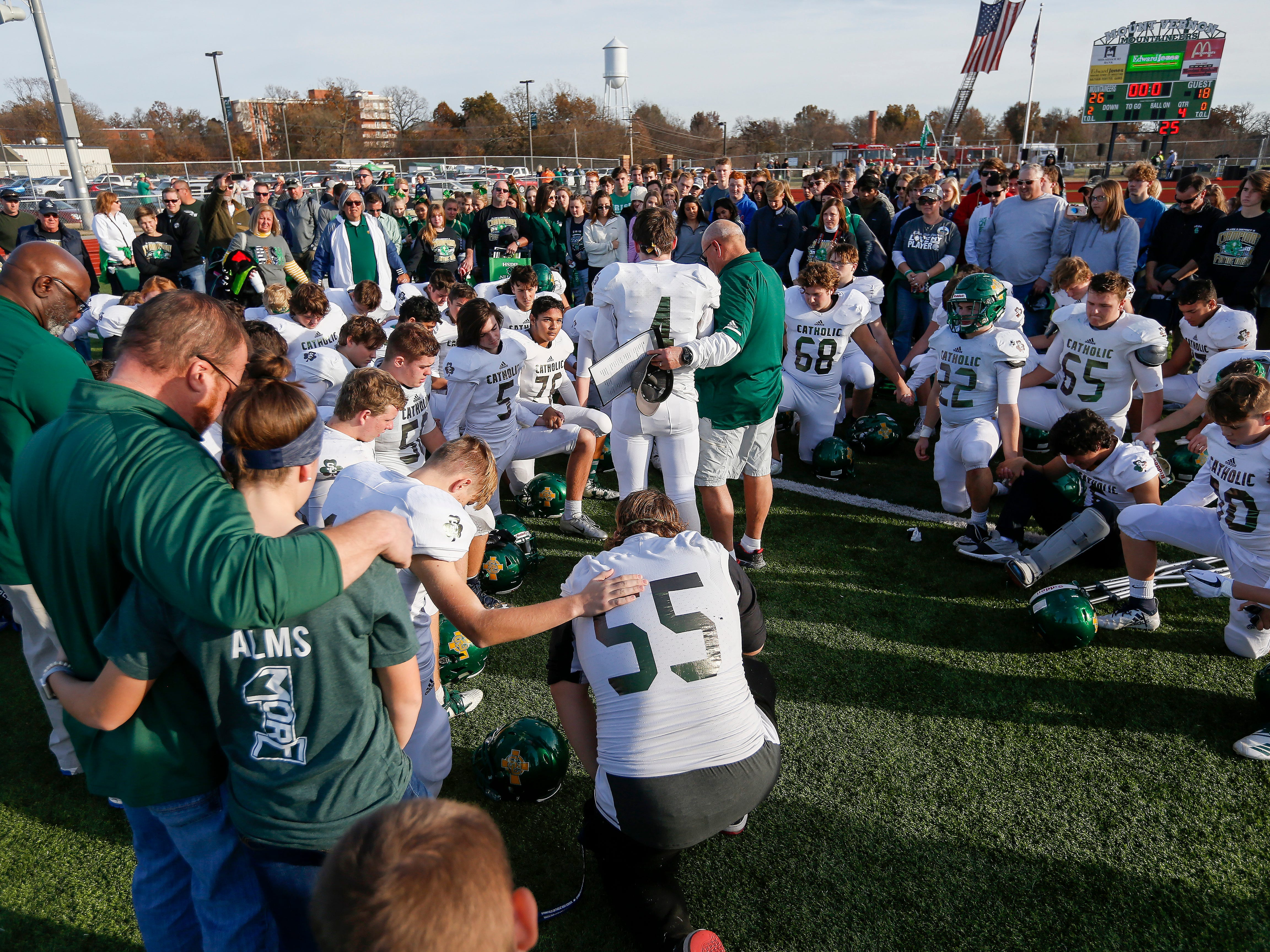 Springfield Catholic players, coaches, family and friends say a prayer after their 26-18 loss in the Class 3 Quarterfinal game against Mount Vernon at Mount Vernon High School on Saturday, Nov. 17, 2018.