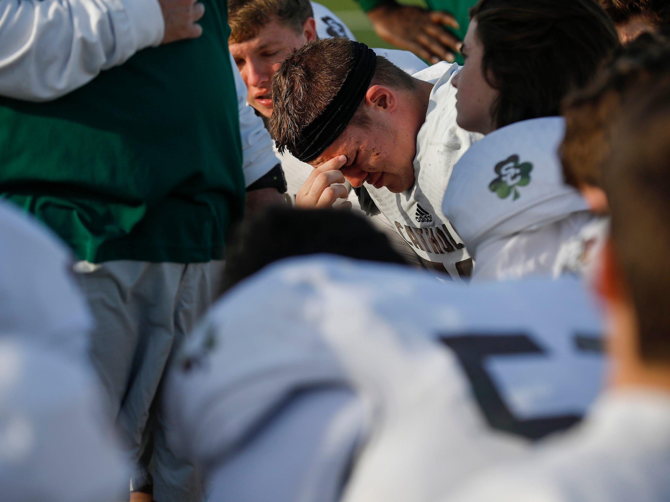 Kye Alms, of Springfield Catholic, center, hangs his head after the Irish's 26-18 loss in the Class 3 Quarterfinal game against Mount Vernon at Mount Vernon High School on Saturday, Nov. 17, 2018.