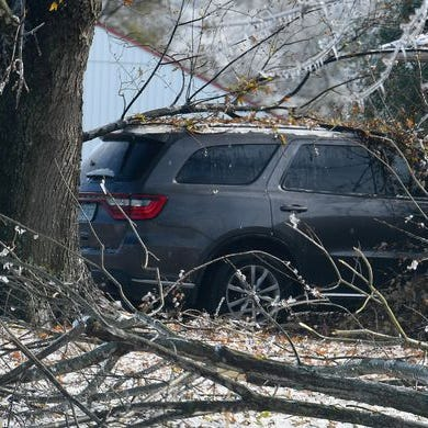 An SUV parked in front a home has fallen branches on top of it at a residence in Fishersville in the wake of an ice storm Friday, Nov. 16, 2018.