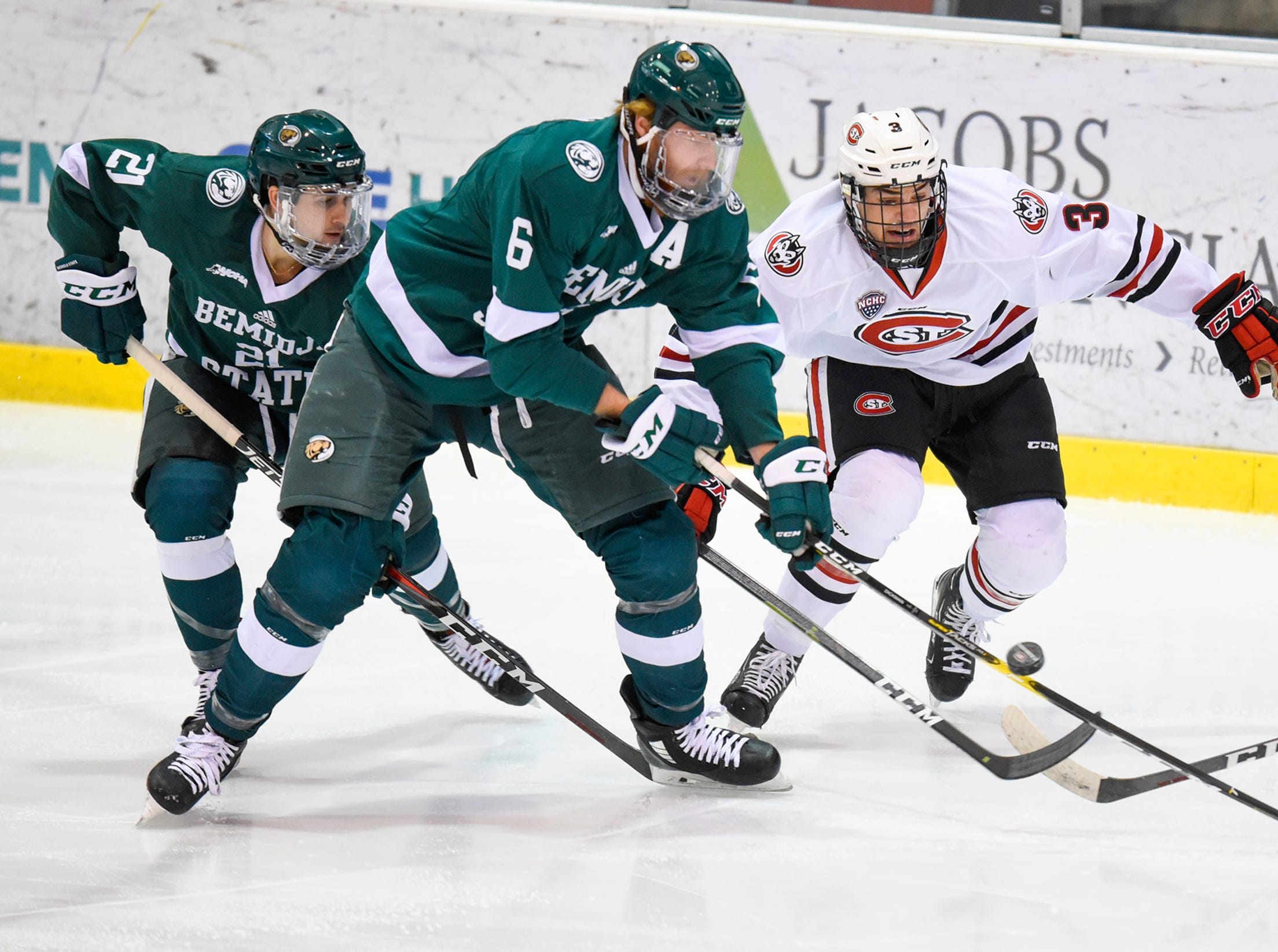St. Cloud State's Jack Poehling and Jay Dickman of Bemidji State concentrate on the puck during the first period of the Friday, Nov. 16, game at the Herb Brooks National Hockey Center in St. Cloud.