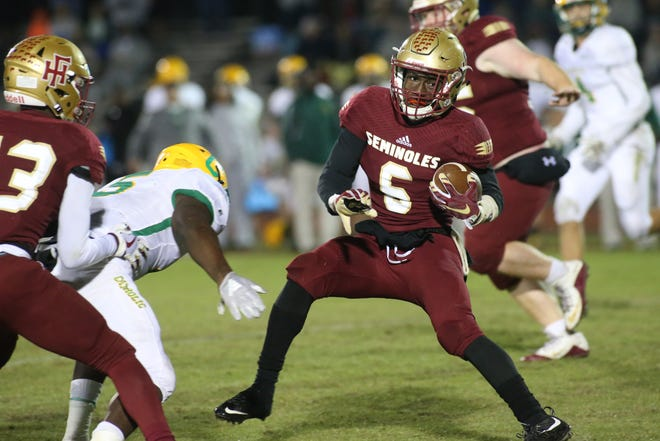 Florida High running back Alfred Menjor dodges his opponents as the Florida High Seminoles take on the Pensacola Catholic Crusaders in high school football, region 1-3A semifinals at Mike Hickman Stadium, Friday, Nov. 16, 2018.