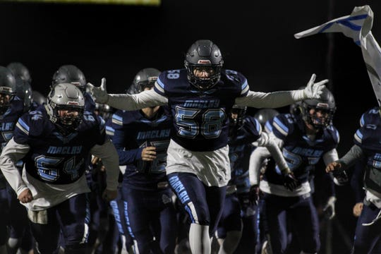 Maclay's Noah Van Syckle (58) leads his team onto the field, as Maclay fell 47-21 to University Christian during a Region 1-2A semifinal on Friday, Nov. 16, 2018.
