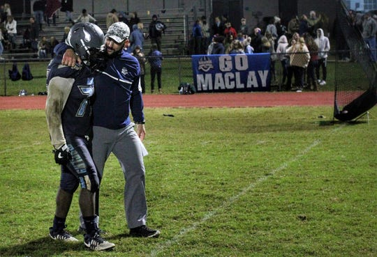 Maclay football coach Lance Ramer consoles senior lineman Eljin Rhymes after Maclay fell 47-21 to University Christian during a Region 1-2A semifinal on Friday, Nov. 16, 2018.