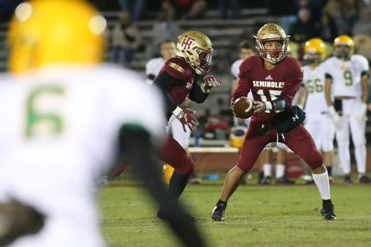 Florida High quarterback Bryson Hill (15) hands off the ball as the Florida High Seminoles take on the Pensacola Catholic Crusaders in high school football, region 1-3A semifinals at Mike Hickman Stadium, Friday, Nov. 16, 2018.
