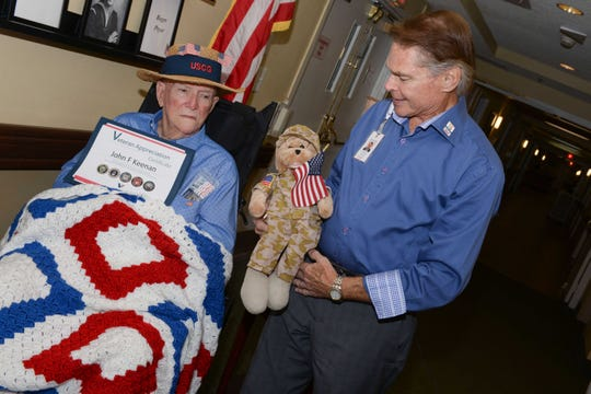 """Treasure Coast Hospice Volunteer Michael Gangloff, right, presents U.S. Coast Guard veteran John Keenan with a patriotic blanket and a G.I. Teddy Bear that sings Lee Greenwood's """"God Bless the U.S.A."""" during a recent visit at The Gardens of Port St. Lucie assisted living facility."""